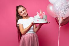 Girl with a cake for a birthday, in the Studio on a pink background, festive mood, close - up, designer cake. Girl with a cake for a birthday, in the Studio on a stock photos