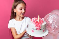 Girl with a cake for a birthday, in the Studio on a pink background, festive mood, close - up, designer cake. Girl with a cake for a birthday, in the Studio on a stock image