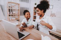 Mom and Girl Time Together. Laptop and Mother. Girl with Cake Mother with Tea. Good Happy Day for Young Girl and Young Mother. Smile Girl and Smile Mother. Cake royalty free stock image