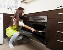Girl with cake near the oven Stock Images