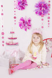 Girl with cake at pink decoration birthday party. Little girl with cake at pink decoration birthday party Royalty Free Stock Image
