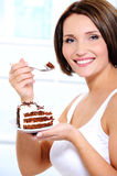 Girl with cake on plate brings  spoon to a mouth Royalty Free Stock Image