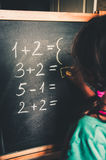 Girl calculating by fingers to write the answer on chalkboard stock image