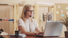 The girl from the call center adjusts the headset, talking to the client and prints the information on laptop . On the