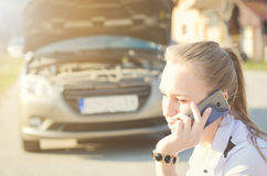 Girl calling. Broken car on a background. Woman sit on a wheel. young woman repair a car. Natural background. Car accide Royalty Free Stock Images