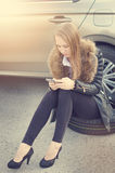 Girl calling. Broken car on a background. Woman sit on a wheel. Sexy young woman repair a car. Natural background. Car accide Stock Photos