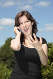 Girl calling by cell phone gesturing w hand Stock Image