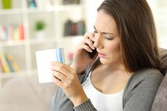 Girl calling doctor asking information about medicine. Worried girl calling doctor asking information about medicines sitting on a sofa in a house interior royalty free stock image