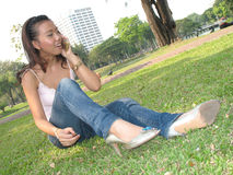 Girl calling friend. Girl sitting in grass with mobile phone Royalty Free Stock Image