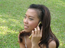 Girl calling friend. Girl sitting in grass with mobile phone Stock Photography