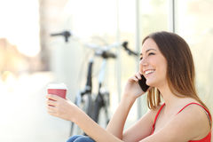 Girl calling on the mobile phone and drinking coffee. Sitting in a park with a bicycle in the background Royalty Free Stock Photography