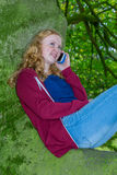 Girl calling with mobile phone in green tree Royalty Free Stock Photo