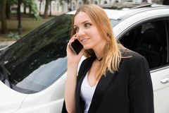 The girl is calling by the phone. Near the car Royalty Free Stock Photography