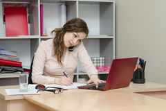 Girl calling by phone and working on laptop Royalty Free Stock Photo