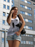Bad news. Young beautiful brunette talking on a mobile phone outdoors in a sun with buildings worried and anxious expression Royalty Free Stock Images