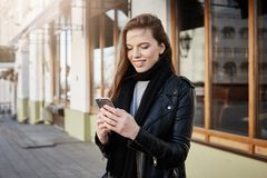 Girl is calling taxi. Beautiful modern woman in trendy clothes holding smartphone and looking at screen while messaging royalty free stock image