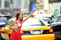 Girl calling taxi cab in New York City. Holding tablet pc computer standing in cute summer dress in street of Manhattan, USA. Beautiful young mixed race Asian Stock Images