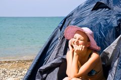 Girl calls by phone, sitting in tent Stock Photos