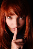 The girl calls for silence. The red-haired girl has brought a forefinger to lips royalty free stock photography