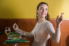 Girl calls up the waiter in a restaurant Royalty Free Stock Image