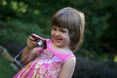 Girl and camera. A little girl playing with a digital  camera Royalty Free Stock Image