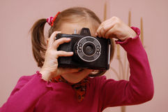 Girl with camera. A young girl taking pictures with an very old type of camera Royalty Free Stock Photos