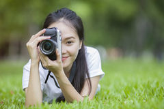 Girl with camera lie down on grass. Close up girl with camera lie down on grass Royalty Free Stock Photography