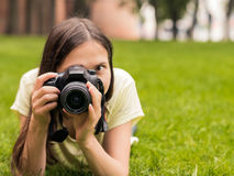 Girl with camera lie down on grass Royalty Free Stock Image