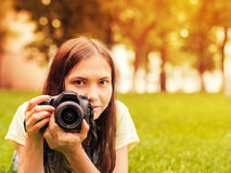 Girl with camera lie down on grass Stock Photography