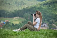 Girl with camera sits on a hill and mountain photographs. Summer Stock Photos