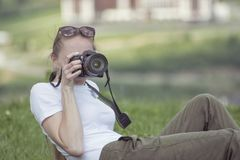 Girl with the camera sits on a hill and photographs. Forest on b Stock Images