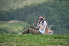 Girl with the camera sits on a hill and photographs. Forest on b Royalty Free Stock Photo