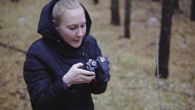 The girl with the camera takes pictures of the autumn forest. late autumn the first snow. cinematic shot, slow motion.й. The girl with the camera takes pictures stock video