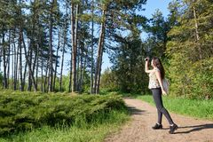 Girl with camera taking pictures of nature in spring, beautiful forest and trees on a Sunny day Royalty Free Stock Photos