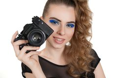 Girl with a camera. Young beautiful girl with makeup and haircut with a camera in her hand isolated on white background. Studio photography Royalty Free Stock Photo