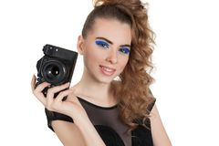 Girl with a camera. Young beautiful girl with makeup and haircut with a camera in her hand isolated on white background. Studio photography Stock Photos