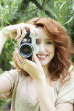 Girl with camera. Young woman photographing with an old analogue photo film camera royalty free stock image