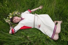 Girl in a camomile chaplet lying from meadow. Girl in a flowers wreath and traditional clothes lying from meadow royalty free stock photos