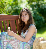 Girl with camomile flower sitting outdoor Royalty Free Stock Photography