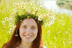 Girl in camomile wreath. Portrait of girl in camomile wreath against nature royalty free stock photography