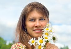 The girl with camomiles. Against the sky stock photography