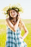 Girl  in camomiles chaplet. Long-haired teen girl  in camomiles chaplet against summer field Stock Photos