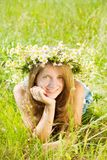 Girl  in camomiles chaplet in grass Stock Photography