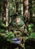 Girl in camouflage clothing to keep a bowl of blueberries in the hands  the forest Royalty Free Stock Image