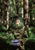 Girl in camouflage clothing to keep a bowl of blueberries in the hands  the forest Royalty Free Stock Photography
