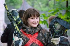 Girl in camouflage after paintball game. Smiling girl in camouflage with a gun after playing paintball stock images