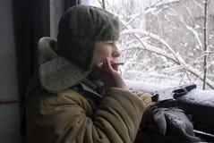 Girl in a camouflage smokes Stock Photos