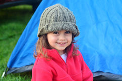 Girl on camping holiday. Young girl on camping holiday smiling while looking at the camera, relaxing outside a tent outdoor. Concept photo of child , children royalty free stock photo