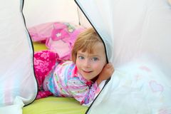 Girl in camping tent lying on camp tent. Girl in camping tent lying happy on camp tent royalty free stock photos