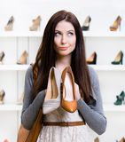 Girl can't choose footwear Royalty Free Stock Photography
